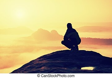 Rear view of male hiker sitting on the rocky peak while enjoying a colorful daybreak above mounrains valley