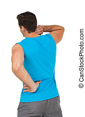 Rear view of man in sportswear suffering from neck ache