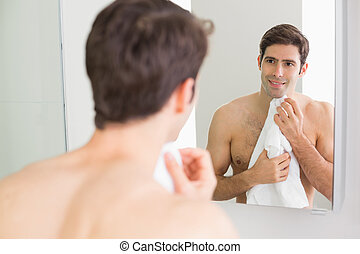 Rear view of man looking at self in bathroom mirror