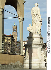 rear view  of marble statue made by Enrico Pazzi dedicated to Dante and  Palazzo Vecchio at the background, Florence, Italy