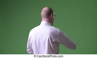 Rear view of mature bald businessman pointing finger and...