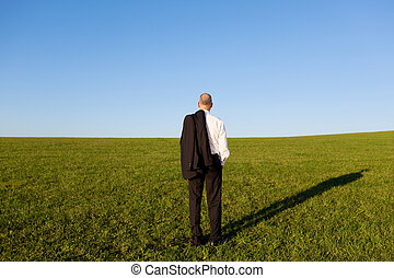 Rear View Of Mature Businessman Standing On Grassy Field
