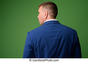 Rear view of mature macho businessman in suit