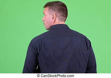 Rear view of mature macho businessman looking over shoulder
