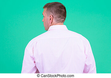 Rear view of mature macho businessman with pink shirt