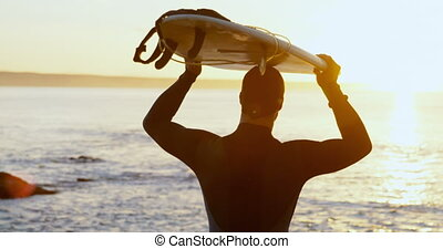 Rear view of mid-adult caucasian male surfer carrying ...