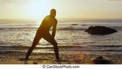 Rear view of mid-adult caucasian male surfer stretching and ...
