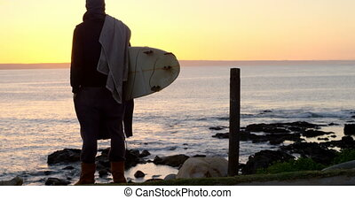 Rear view of mid-adult man with surfboard standing near ...