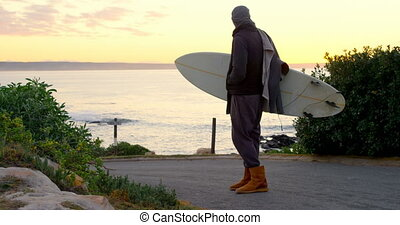 Rear view of mid-adult man with surfboard standing on road ...