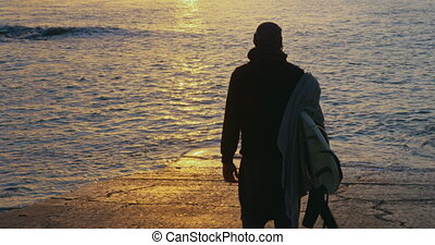 Rear view of mid-adult man with surfboard walking on the ...