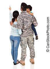rear view of military family pointing empty space isolated...
