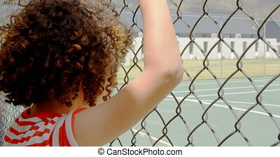 Rear view of mixed-race schoolgirl standing near wire mesh ...