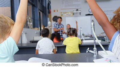 Rear view of mixed-race schoolkids raising hands in the classroom 4k