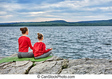 Rear view of mother and daughter practicing yoga on rocks near river.