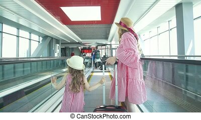 Rear view of mother and little daughter holding hands walking to the waiting room in airport