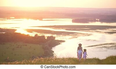 Rear view of mother and little daughter holding hands walks down the hill with perfect view on the river at sunset