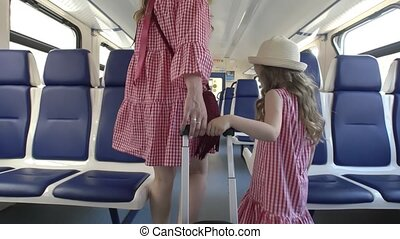 Rear view of mother and little daughter in same dresses walks in empty train car