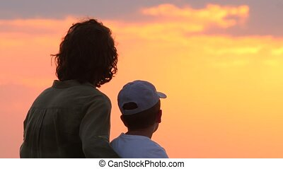 Rear view of mother and son at sunrise. Interpersonal ...