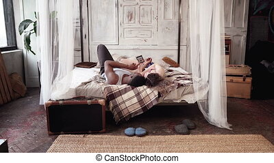Rear view of multiracial couple lying on the bed and use smartphone. African man and european woman looks photos.