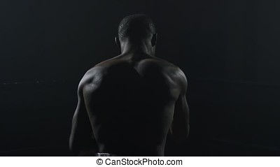 Rear view of muscular man boxing on black background. Afro american young male boxer practicing shadow boxing