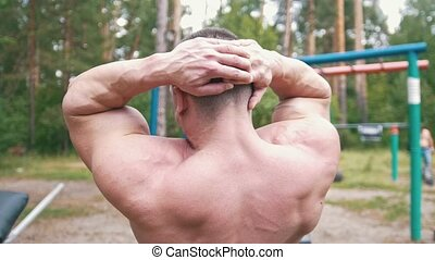 Rear view of muscular man doing exercises for abs muscles at...