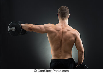 Rear View Of Muscular Man Lifting Dumbbell