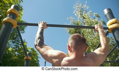 Rear view of muscular man pulled-up on horizontal bar...