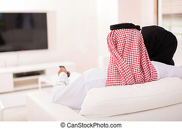 rear view of muslim couple watching tv at home