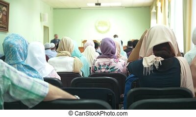 Rear view of muslim women in hijab at the islamic mass...