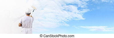 Rear view of painter man painting the blue sky on blank wall, with paint roller isolated on white big space panorama