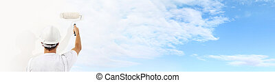 Rear view of painter man with paint roller painting the blue sky and clouds on blank wall, isolated on white