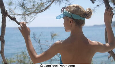 Rear view of relaxed woman on summer travel vacation to the coast sea.