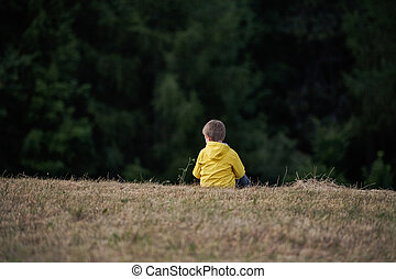 Rear view of school child sitting on field trip in nature, resting.