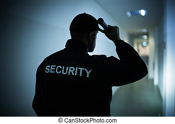 Security Guard With Flashlight In Building Corridor