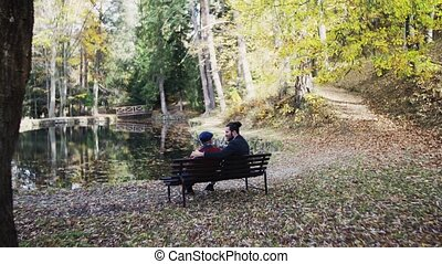 Rear view of senior father and his young son sitting on bench in nature, talking.
