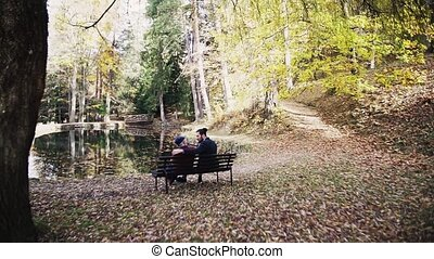 Rear view of senior father and his young son sitting on bench in nature, talking. Slow motion.