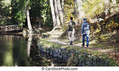 Rearview of senior father and his young son walking by lake in nature, talking.