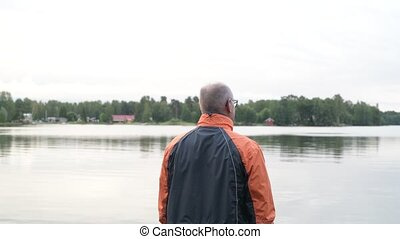 Rear View Of Senior Man Enjoying The View Of The Lake -...