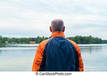 Rear View Of Senior Man Enjoying The View Of The Lake