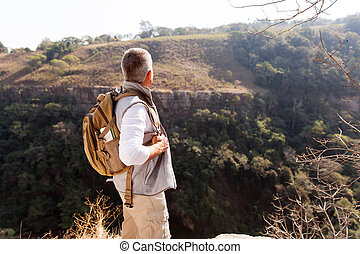 rear view of senior man with backpack