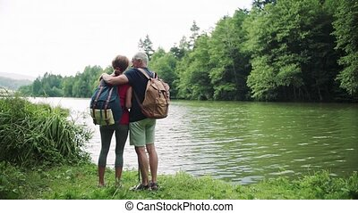 Rear view of senior tourist couple on a walk in nature, standing by lake.