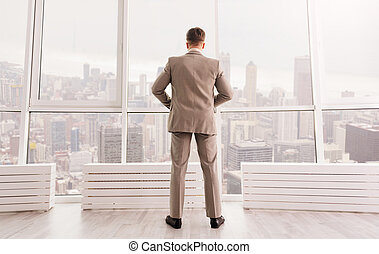 Rear view of serious businessman standing in the office