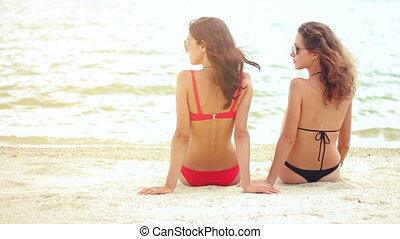 Rear view of sexy women in swimsuit sitting on sandy beach