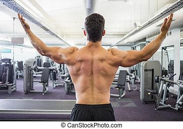 Rear view of shirtless muscular man in gym