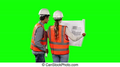 Rear view of site workers looking at the site map with green screen
