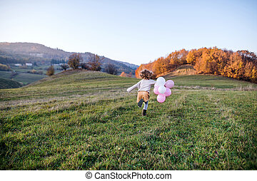 Rear view of small girl with balloons running in autumn nature.