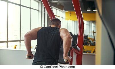 Rear view of strong man training his bicep in a gym