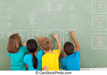 rear view of students learning chinese writing on chalkboard...
