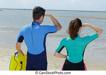 rear view of surfing couple observing the flat sea