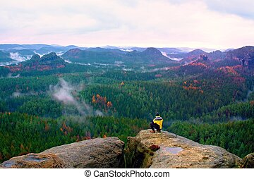Rear view of tall hiker in yellow black jacket on rocky peak while enjoying a daybreak above fall mountains valley